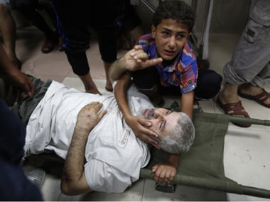 A Palestinian boy cries as he comforts his father wounded by Israeli shelling near a market in Shejaia. Reuters Image