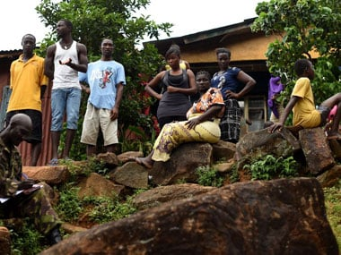 A family in Sierra Leone watches as a soldier enforces quarantine. AFP.