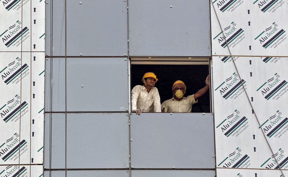 "Labourers look out from a window of a data centre building under construction at the Gujarat International Finance Tec-City (GIFT) at Gandhinagar, in the western Indian state of Gujarat, April 10, 2015. India's push to accommodate a booming urban population and attract investment rests in large part with dozens of ""smart"" cities like the one being built on the dusty banks of the Sabarmati river in western India. Picture taken April 10, 2015.  REUTERS"