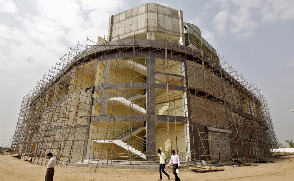 "Engineers walk past a cooling system plant under construction inside Gujarat International Finance Tec-City (GIFT) at Gandhinagar, in the western Indian state of Gujarat, April 10, 2015. India's push to accommodate a booming urban population and attract investment rests in large part with dozens of ""smart"" cities like the one being built on the dusty banks of the Sabarmati river in western India. Picture taken April 10, 2015.  REUTERS"