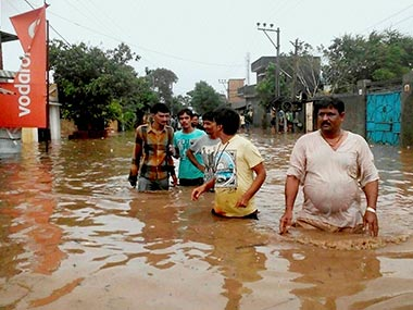 People wade through a water logged street after heavy downpour in Amreli, West Gujarat. PTI
