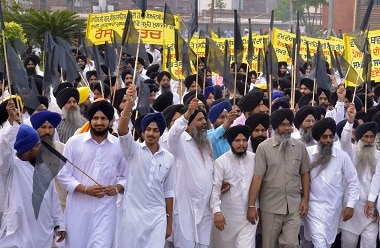Activists from The Shiromani Gurdwara Parbandhak Committee (SGPC) hold black flags as take part in a protest in Amritsar on 20 October against the alleged desecration of a Guru Granth Sahib, the holy book of Sikhs. AFP