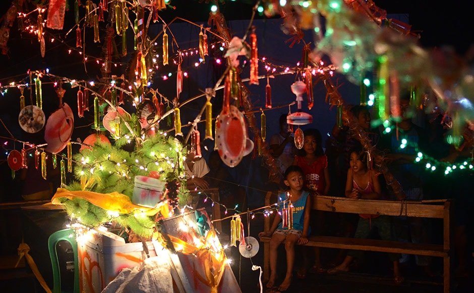 TACLOBAN,-LEYTE,-PHILIPPINES---DECEMBER-24-Survivors-cheer-after-a-Christmas-tree-they-built-using-storm-debris-is-lit-up-on-Christmas-eve-on-December-24,-2013-in-Tacloban,-Leyte,-Philippines
