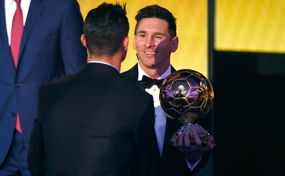 Lionel Messi holds his trophy as he shakes hands with Cristiano Ronaldo after receiving the 2015 FIFA Ballon d'Or. AFP