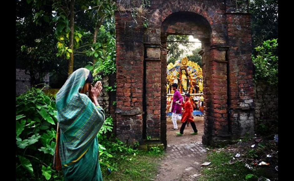 A faithful offers prayers to Goddes Durga during the immersion ceremony on the last day of the Durga Puja festival. Pinak Pramanik, a 28-year-old government employee, shot the photo at Guptipara, Hooghly district in West Bengal.
