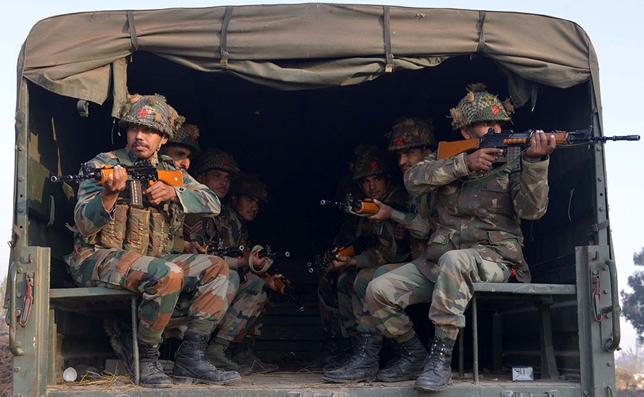 Indian army personnel sit in the rear of a truck in Pathankot on Sunday. Seven security personnel were killed in an attack on army base in Pathankot. AFP