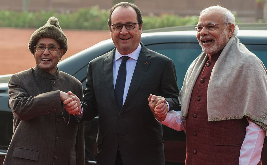 French President Francois Hollande smiles as he holds the hands of Indian President Pranab Mukherjee (L) and Indian Prime Minister Narendra Modi (R) as they pose for a photograph at an official welcoming ceremony in New Delhi on January 25, 2016. After beginning a three-day visit to India in the northern city of Chandigarh on January 24, French President Francois Hollande has headed to the capital New Delhi to make common cause with India's Prime Minister Narendra Modi on issues such as combating Islamist extremists and climate change. AFP PHOTO /ROBERTO SCHMIDT