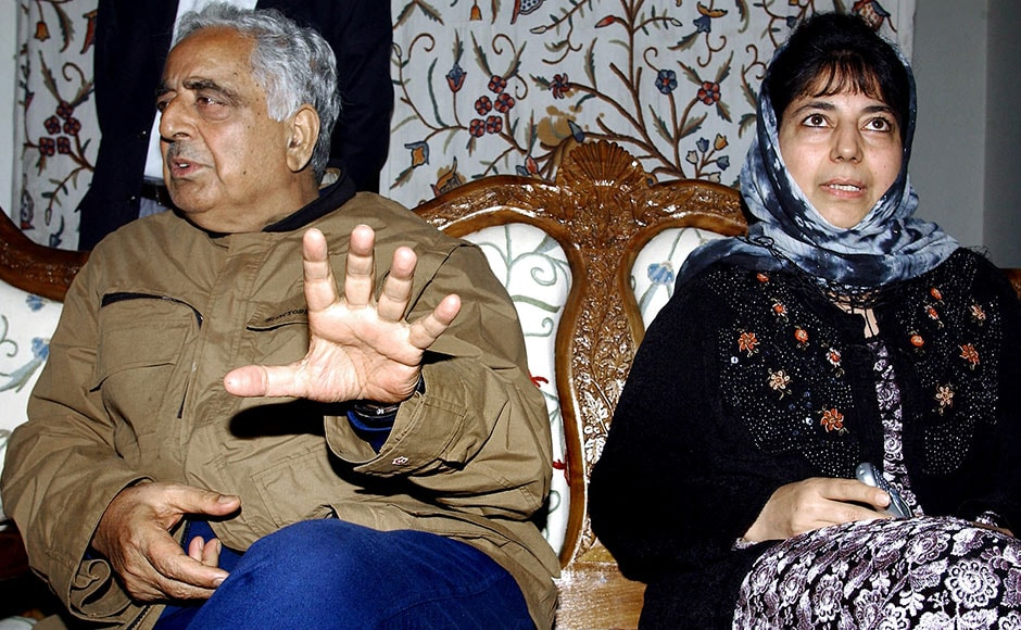 Chief Minister of the Indian state of Jammu and Kashmir Mufti Mohammad Sayeed (R) speaks to civillians rescued from a shopping complex where alleged militants are believed to be in hiding, as his daughter Mehbooba Mufti looks on in Srinagar, 17 October 2003. Two soliders of the Border Security Force were killed and an officer and two press photographers injured in a militant attack. AFP