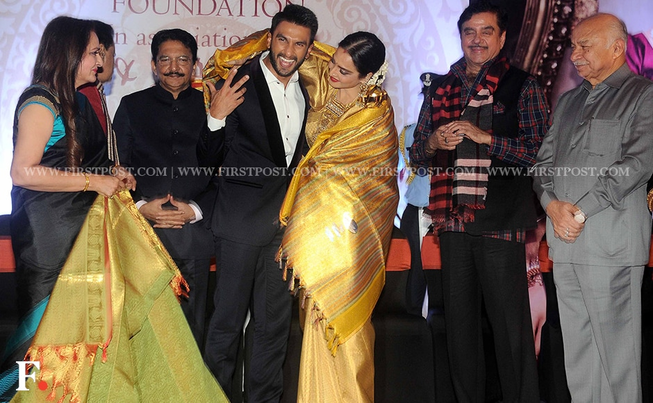 """Rekha shares a hug with Ranveer Singh on stage as other guests look on. On receiving the award, the veteran actress said, """"Am honoured to be bestowed this award in Yash ji's memory. Yash ji thought me how to love and I am eternally grateful for the memories and films that I have had the privilege to be a part of. I can only say that this is not the climax, this is only the best phase of my life and there is a lot more to come. What I learnt from Yash ji is that if you love someone then you should love with all your heart so that there is no scope of loving anything else."""" Firstpost/Sachin Gokhale"""