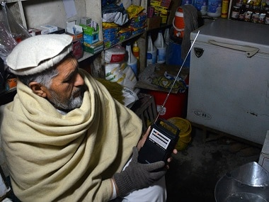 An Afghan shopkeeper, listens to Islamic State Radio at his shop in Jalalabad. AP