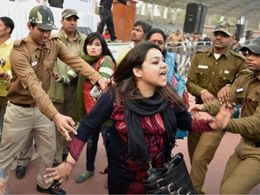 """Policemen try to control a member of Aam Aadmi Sena after she splattered Delhi CM Arvind Kejriwal with ink while protesting against the CNG scam, at a """"thanksgiving rally following the """"success"""" of his government's odd-even scheme at Chhatrasal Stadium, in New Delhi on Sunday. PTI"""