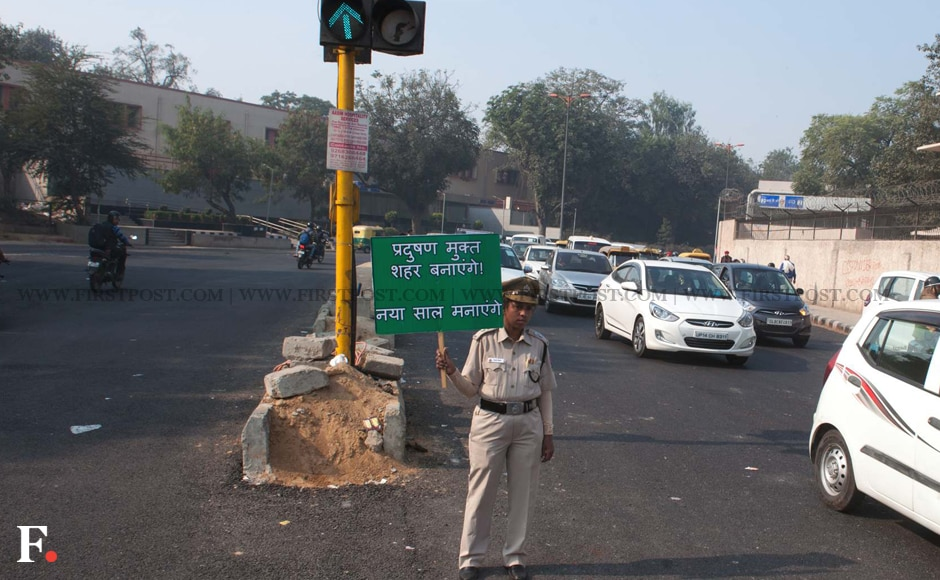 A police personnel holds up a placard for a 'pollution-free city.' The initiative will be tried out over a period of 15 days starting from 1 January. Image: Naresh Sharma/Firstpost
