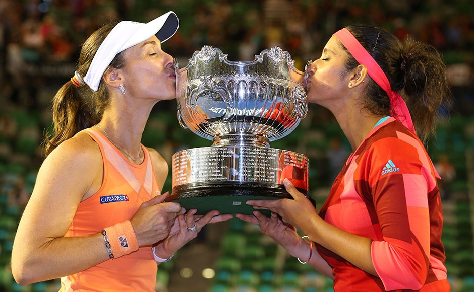 Martina Hingis and Sania Mirza plant a kiss on the Australian open trophy. Getty Images