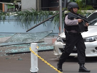 An Indonesian anti-terror policeman (Gegana Brimob) walks next to the Starbucks cafe near site of the attacks in Jakarta. AFP