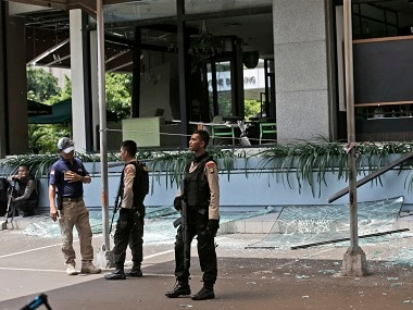 Police officers stand guard outside a damaged Starbucks cafe after an attack in Jakarta on Thursday. AP