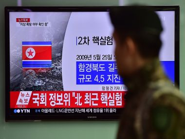 A South Korean soldier walks past a television display showing a news report, after seismologists detected a 5.1 magnitude tremor next to North Korea's main atomic test site. AFP