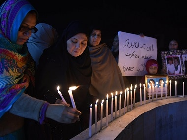 Relatives of the 2014 Peshawar school attack victims light candles for the victims of the Bacha Khan university in Peshawar. AFP