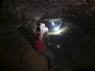 A Palestinian worker sits inside a smuggling tunnel in this file photo. Reuters