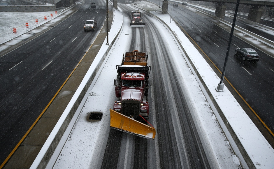Snowplow trucks work on the roads as the snow begins to fall in Washington. Several states have declared a state of emergency following the snowstorm. Reuters.