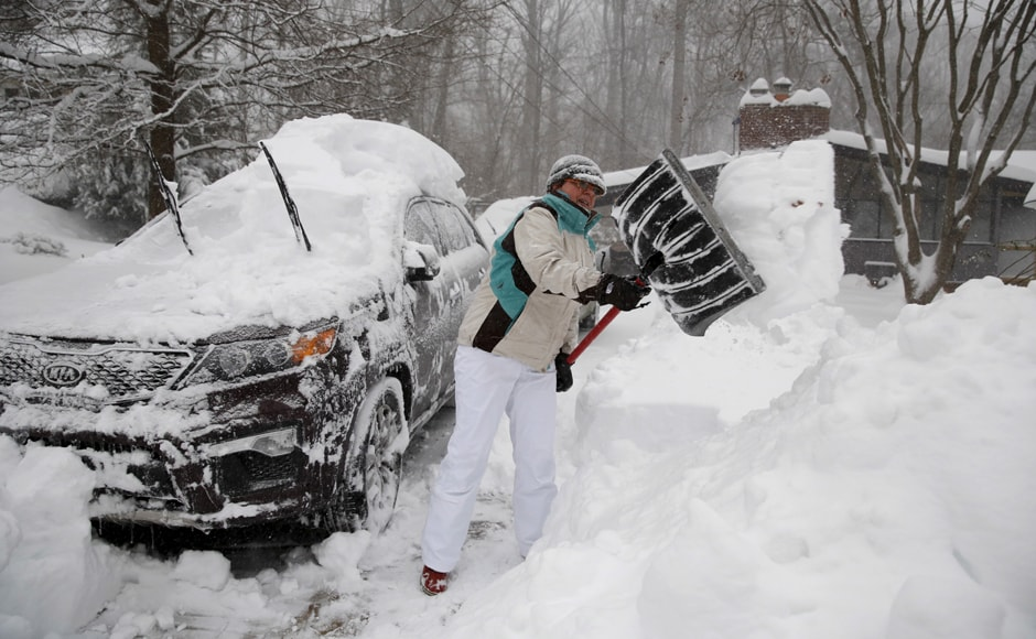 A woman in Virginia digs out her car as a blizzard hits the east coast January 23, 2016. A major snowstorm has left almost the entire eastern coast of the US paralysed. Reuters.
