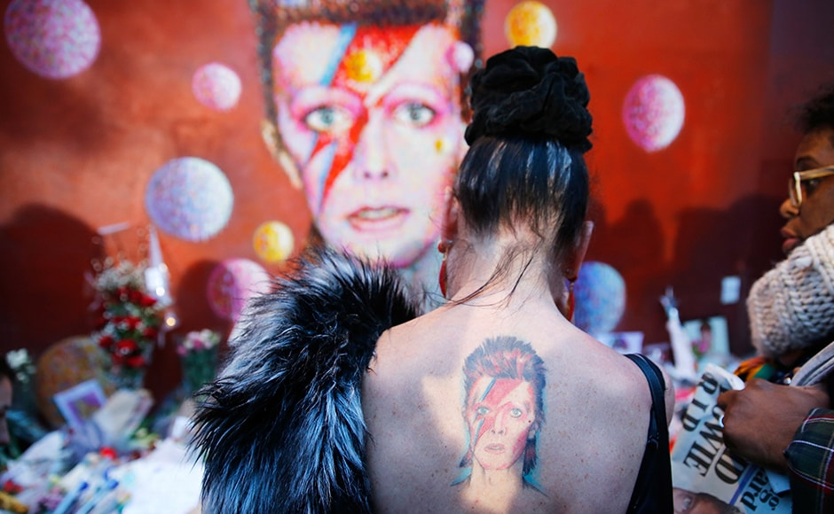 A woman with a Ziggy Stardust tattoo visits a mural of David Bowie in Brixton, London after news of the music legend's demise broke on Monday. Thousands mourned his passing all over the world. Reuters
