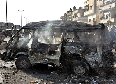 Syrian citizens gather at the scene where twin bombs exploded at a government-run security checkpoint, at the neighborhood of Zahraa, in Homs province, Syria. SANA via AP