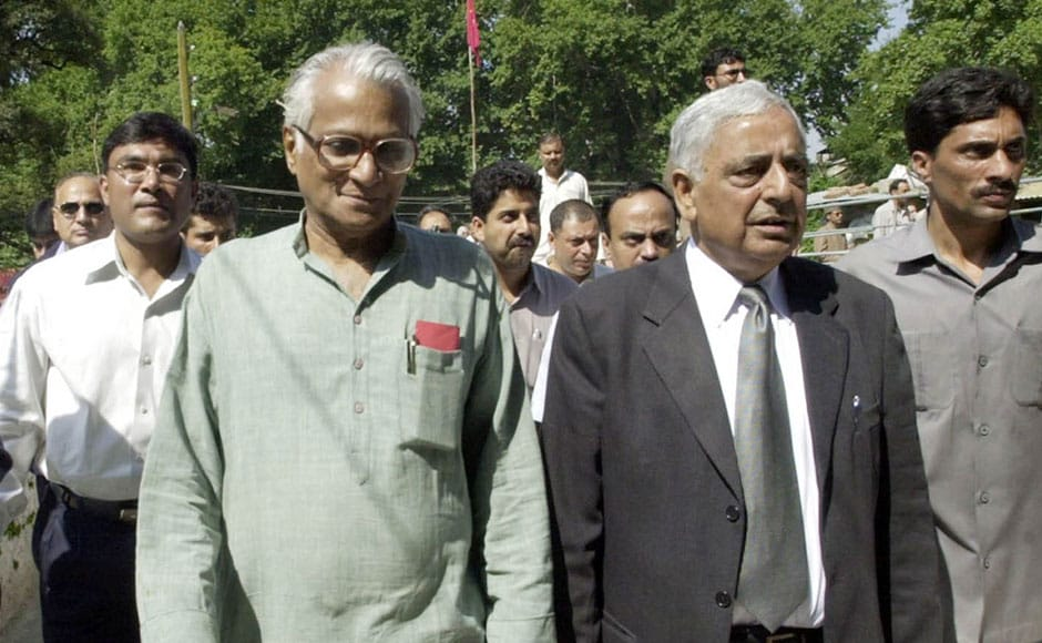 George Fernandes and Mufti Mohammad Sayeed walk with security personnel during a function at Mattan, some 60 kms south of Srinagar, on 14 September, 2003. Fernandes' visit comes as two Indian security force troops and a civilian were killed and four other people injured in two separate incidents in the Himalayan state. AFP