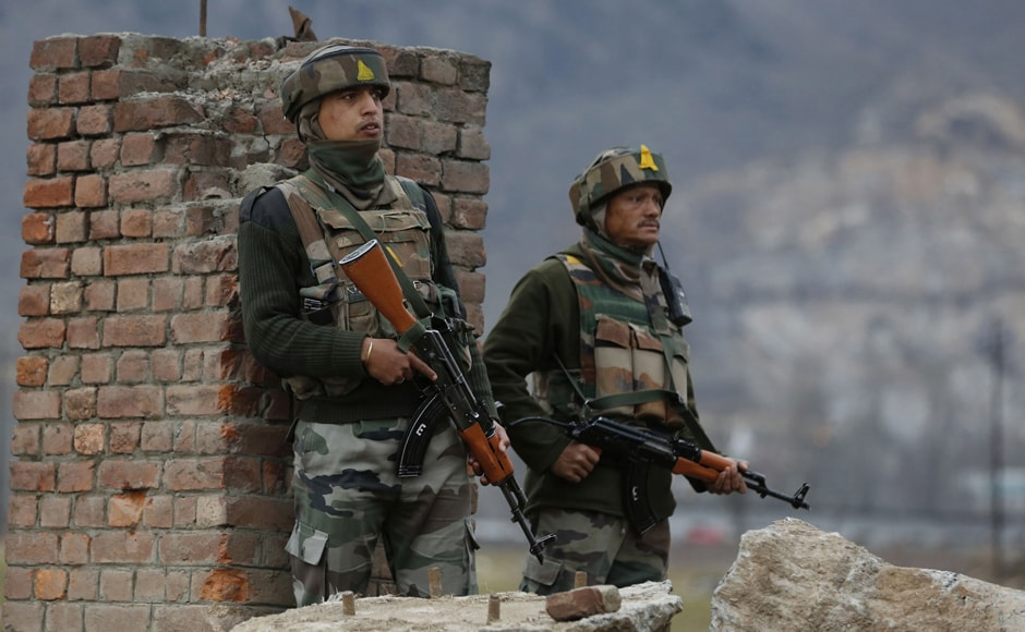 Indian military personnel stand near a building taken over by militants at Pampore, some 15 kms south of Srinagar. Suspected terrorists attacked a paramilitary convoy in J&K. Counter-terrorism are continuing on Monday. AFP