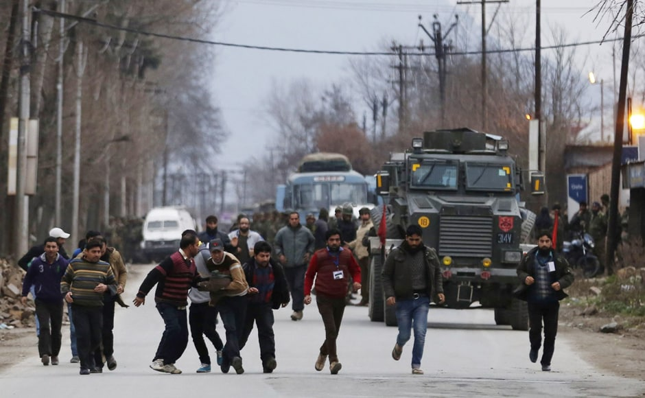 Kashmiri residents run to safety after being rescued from a building taken over by suspected militants during clashes in Pampore on 20 February. AFP