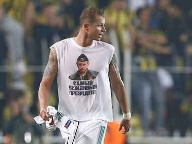 """Lokomotiv Moscow's Dmitri Tarasov wearing a t-shirt depicting Russian President Vladimir Putin leaves the pitch after the match. The sign reads, """"Most polite president"""". Reuters"""