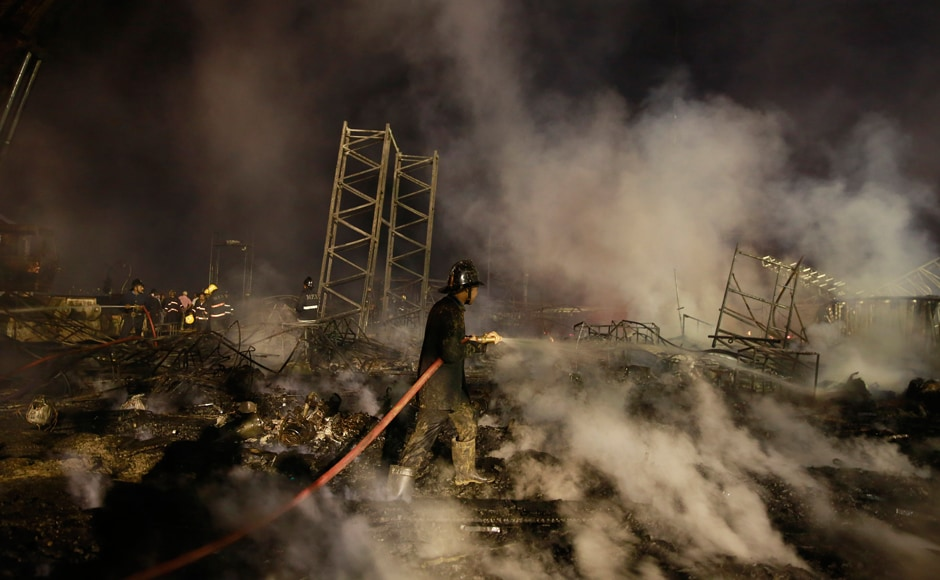 A fire fighter douses the fire which broke out during an event held for 'Make in India Week'. AP/Rafiq Maqbool