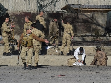 Afghan security personnel gather as victims are treated at the site of a suicide car bomb next to a police base in Kabul. AFP