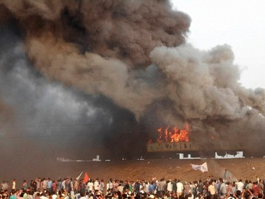 A file image of agitators from the Kapu community setting coaches of Ratnachal Express to fire. PTI