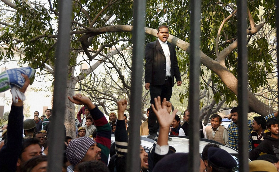A lawyer stands on a car while shouting slogans at Patiala House Court. PTI