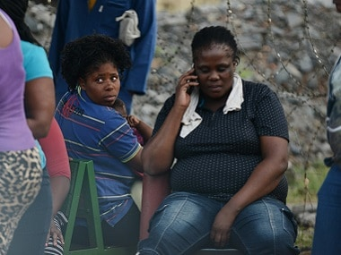 Concerned family members and friends of three missing persons sit outside the Vantage Goldfields Limited's Lily Mine's entrance near Barberton, South Africa. AP