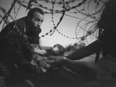 """This picture released by the World Press Photo was taken by Australian freelance photographer Warren Richardson on 28 August, 2015 in Roszke, Hungary. It shows a refugee passing a baby under a barbed wire fence at the Hungarian-Serbian border. It is titled """"Hope for a New Life"""". Warren Richardson / World Press Photo / AFP"""