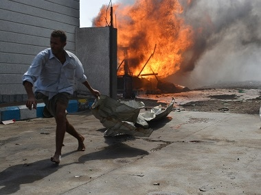 A man runs away from a petrol station after it was hit by a Saudi-led air strike in Yemen's Red Sea port city of Houdieda on 5 February. Reuters