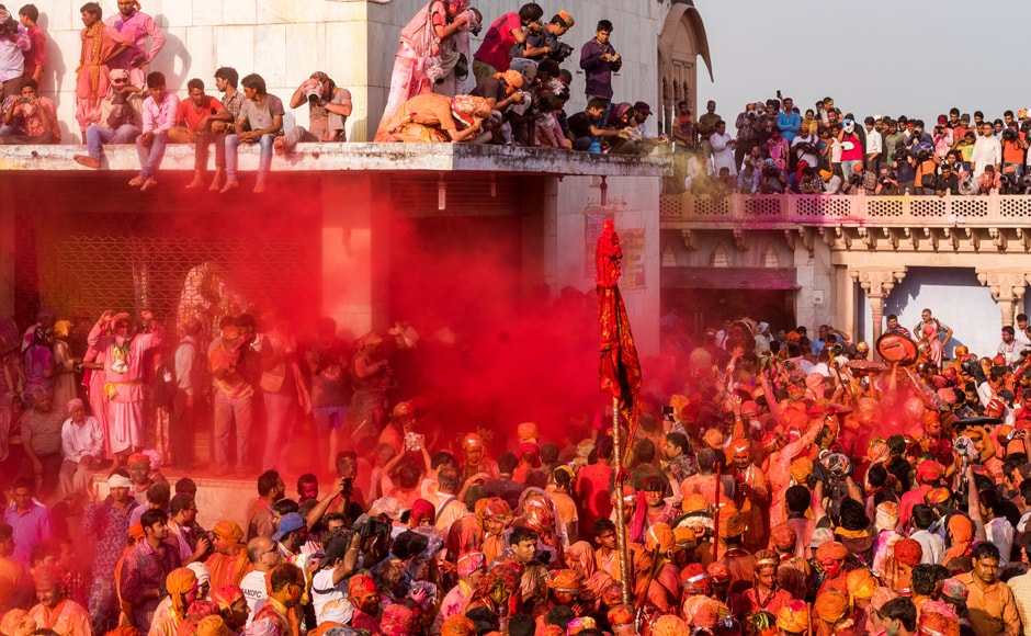 As the villagers of Nandgaon were busy throwing colours on each other, some others took the opportunity to perch on top of building to take photos. AFP
