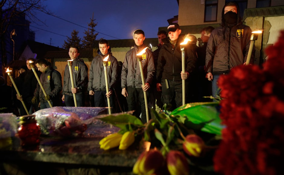 Servicemen of Azov, Ukrainian volonteers battalion, hold torches in front of floral tributes during a ceremony in front of the Belgian embassy in Kiev on 22 March, in tribute to the victims of Brussels. AFP