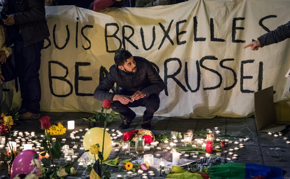 "People hold a banner reading in French and Flamish ""I am Brussels"" as they gather around floral tributes, candles, belgian flags and notes in front of the Bourse of Brussels on 22 March in tribute to the victims of Brussels. AFP"