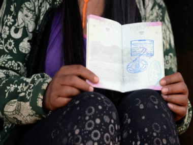 This photo taken on January 25, 2016 shows Nepalese migrant worker Sunita Magar, who was trafficked to Syria, holding her passport at home in Dhadhing district.  AFP