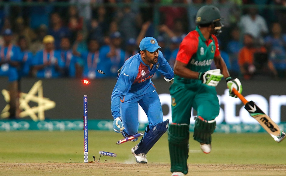 Cricket - India v Bangladesh - World Twenty20 cricket tournament - Bengaluru, India, 23/03/2016. India's captain and wicketkeeper Mahendra Singh Dhoni (L) runs out Bangladesh's Mustafizur Rahman. REUTERS
