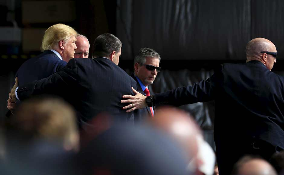Secret Service agents surround US Republican presidential candidate Donald Trump during a disturbance as he speaks at Dayton International Airport in Dayton, Ohio. Reuters