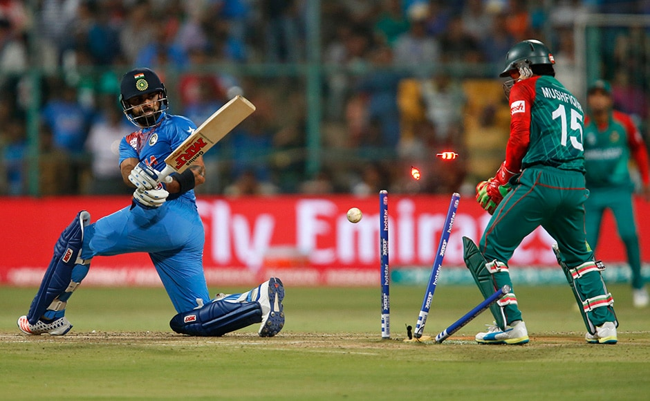 Cricket - India v Bangladesh - World Twenty20 cricket tournament - Bengaluru, India, 23/03/2016. India's Virat Kohli (L) is bowled as Bangladesh's wicketkeeper Mushfiqur Rahim looks on. REUTERS/Danish Siddiqui - RTSBWN7