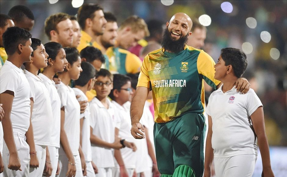 Hashim Amla shares a cheerful moment with a young macot before the national anthems. PTI