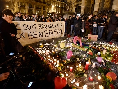 """People holding a banner reading """"I am Brussels"""" behind flowers and candles to mourn for the victims at Place de la Bourse in the centre of Brussels on Tuesday. AP"""