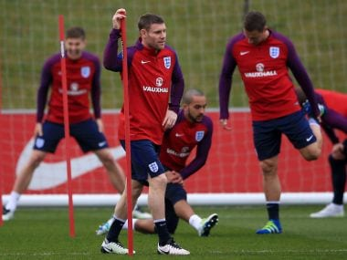 England's James Milner and other team members warm up during a training session. AP