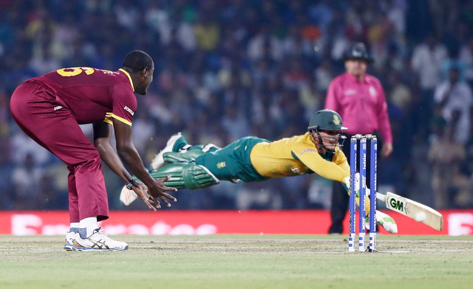 At full stretch: South Africa's Quinton De Kock dives to make his ground as West Indies' Carlos Brathwaite waits to collect the ball. AP