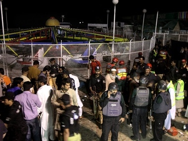 Pakistani police officers and rescue workers gather at the site of the bomb explosion. AP