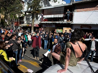 Arturo Hernandez sits on a car wearing a dress to get the driver to move from a clogged street in Mexico City. AP